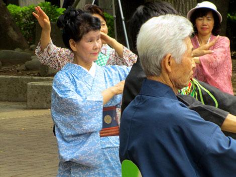 Eine Gruppe Japaner in traditionellen Kostümen, die gemeinsam im Park tanzen