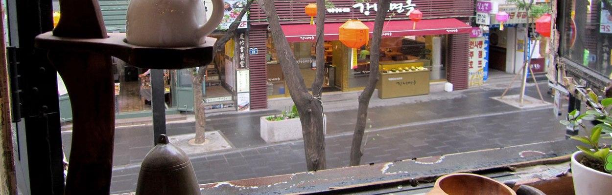 Blick aus dem mit Teekanne und Pflanzen dekorierten Fenster einer koreanischen Teestube aus dem ersten Stock hinab auf eine verregnete Einkaufsstraße in Seoul