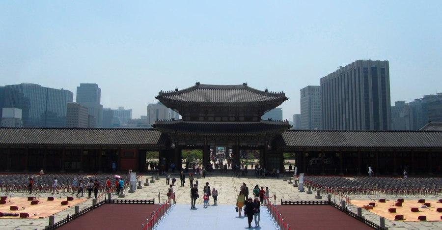 Blick auf das Eingangstor - vom Innenhof gesehen - des Gyeongbokgung Palastes mit den Hochhäusern Seouls im Hintergrund.
