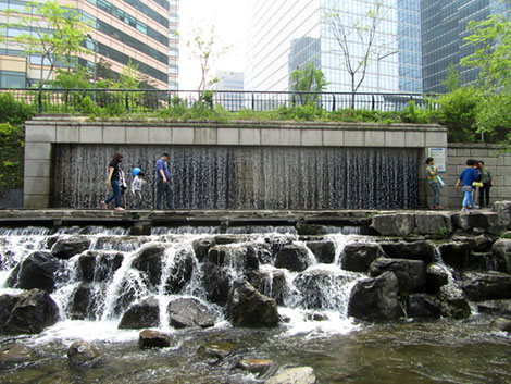 Künstlicher Wasserfall am Cheonggye Stadtbach. Passanten spazieren den Weg entlang.