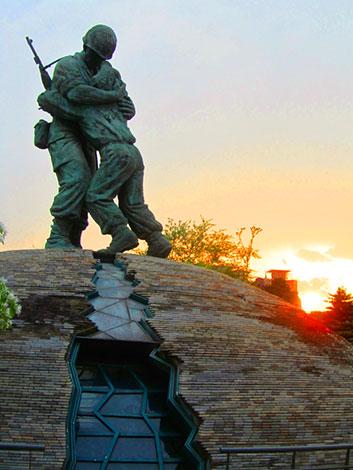 Standbild in Erinnerung an den Korea Krieg. Zwei Soldaten liegen sich in den Armen, unter ihnen ein Riss.