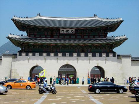 Das Eingangstor des Gyeongbokgung Palastes von der Straße aus gesehen. Davor: viel Straßenverkehr.