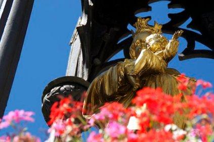Eine goldene Marienstatue mit Kindlein und roten Geranien davor