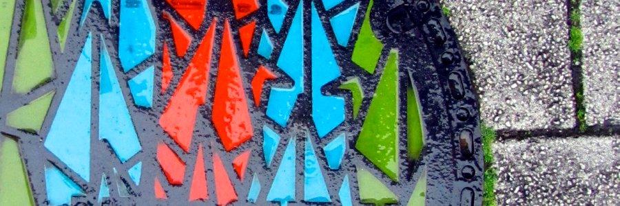 """Bunter Kanaldeckel in Hiroshima - mit Beschriftung """"Hiroshima"""" und stilisierten Papierkranichen (Header)"""