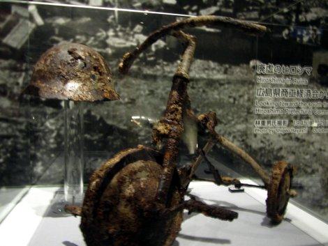 Das verrostete Dreirad und der verrostete Stahlhelm eines kleinen Jungen, der an den Folgen der Atombombe auf Hiroshima starb