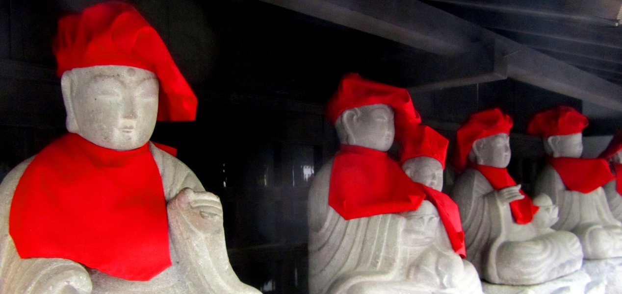 Eine Reihe Steinbilder von Mönchen, die rote Mützen und Umhänge tragen (Header des Artikels)