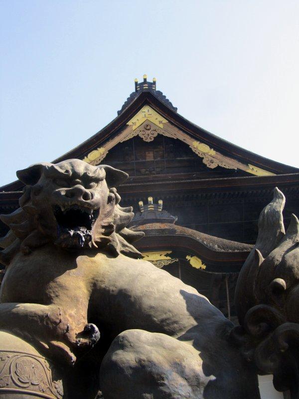 Ein steinerner Löwe bewacht die Tempelhalle in Nagano