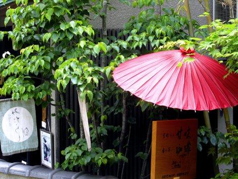 Geschäft mit rotem Sonnenschirm an Kyoto's Philosophenweg