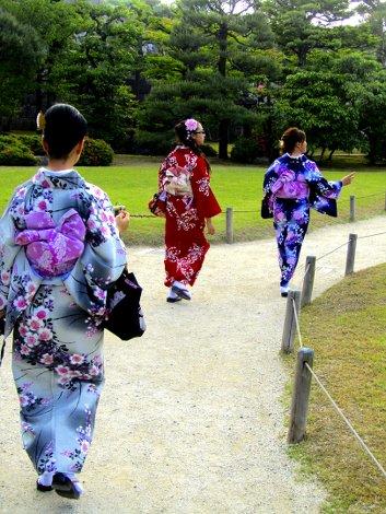 Drei junge Frauen in farbenfrohen Kimonos, von hinten fotografiert