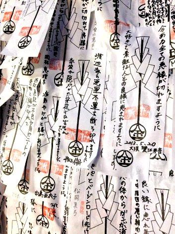 Tausende Zettel mit Gebeten bedecken diesen Stein (den man nicht mehr sehen kann) in einem Schrein in Gion