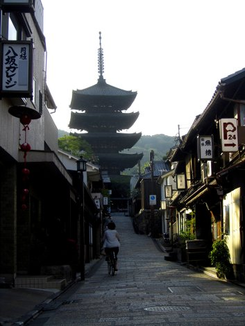 Eine Gasse in Gion führt hinauf zu einer Pagode, eine Fahrradfahrerin fährt daraufhin zu