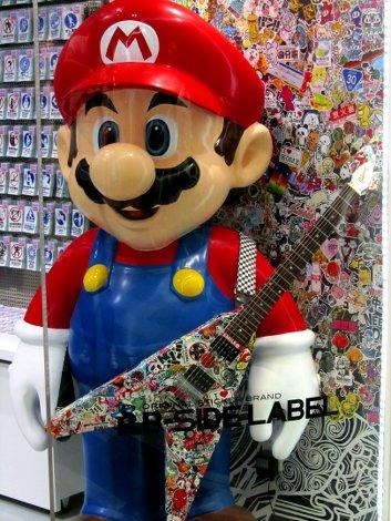 Eine große Super Mario Figur steht mit einer comicfarbenen E-Gitarre im Schaufenster