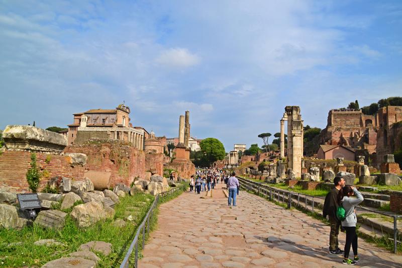 Forum Romanum: die Pflastersteine der Via Sacra, links und rechts Ruinen, ganz in der Ferne der Titus-Bogen, rechts der Palatin