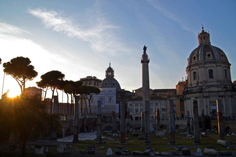 Eine Reihe von Säulen sind von der Kaiserforen übrig geblieben, dahinter zwei kleine Kirchen mit Kuppeldächern, die goldene Sonne verschwindet hintern den Häusern des modernen Roms