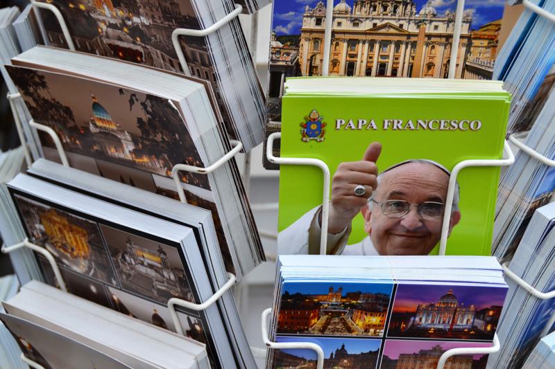 Postkartenständer mit grell-grüner Karte, die Papst Franziskus mit hochgestreckten Daumen zeigt.
