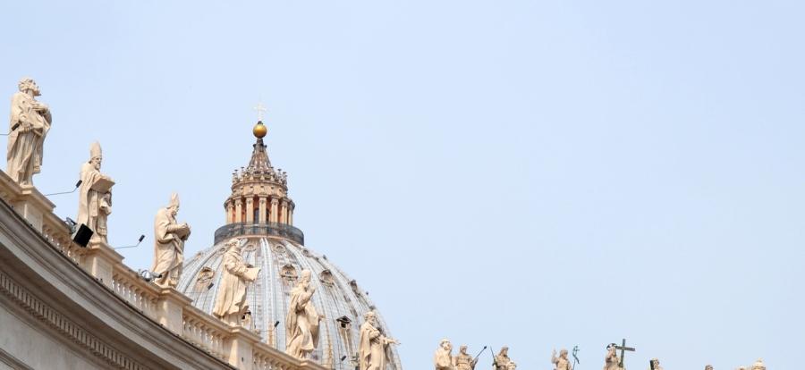 Die Säulenhalle zur linken Seite des Petersdom; die Kuppel ragt in den Himmel; Statuen von Heiligen stehen auf dem Dach der Säulen