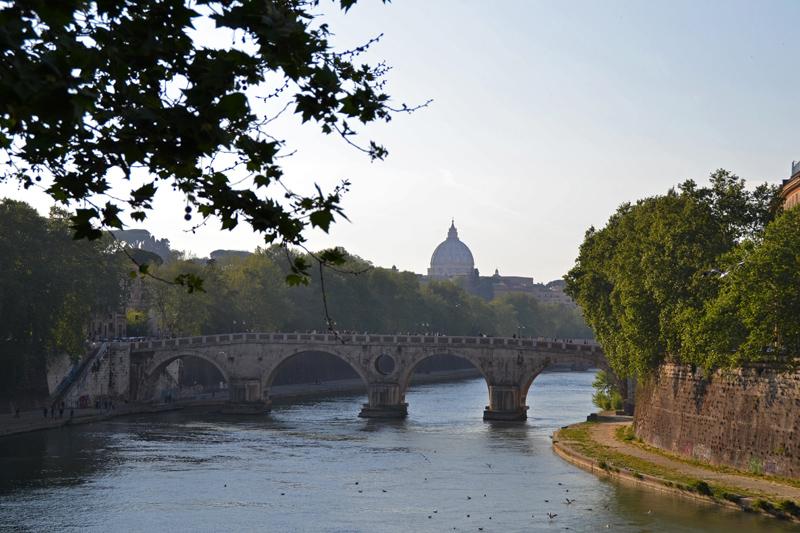 Blick über den Tiber, über eine Brücke, in der Ferne die mächtige Kuppel des Petersdoms