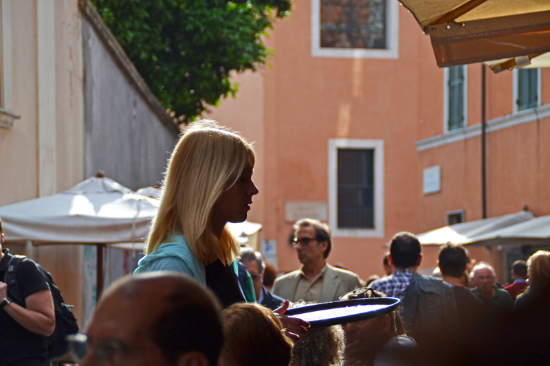 Eine junge, blonde Kellnerin in einem Straßencafé in Trastevere