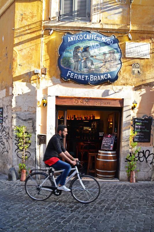 Ein junger Mann fährt mit seinem Rad an einer Bar in Trastevere vorbei
