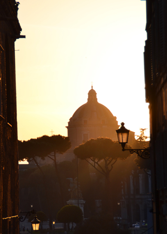 Goldenes Abendlicht fällt über die Kuppel einer Kirche hinein eine Gasse im Viertel Monti