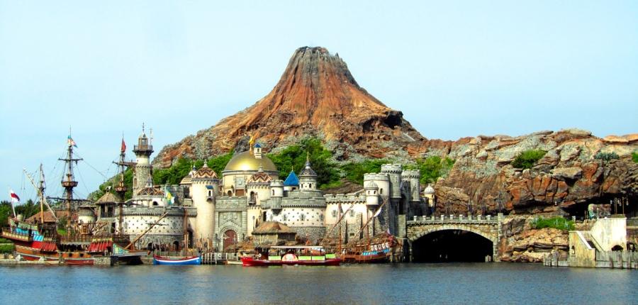 Blick über die große Lagune von Tokyo DisneySea auf eine mittelalterliche Festung mit goldenem Dom, einem alten Segelschiff und dahinter ein Vulkan