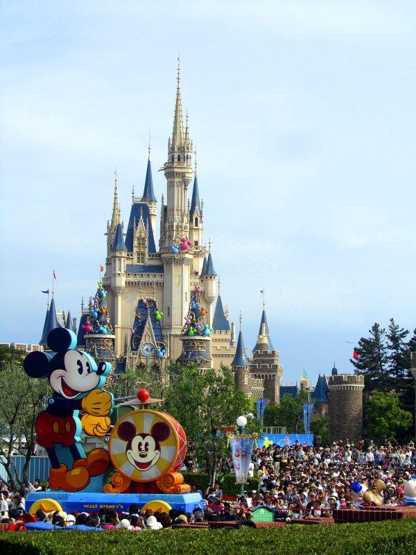 Parade: der Eröffnungswagen zeigt eine riesengroße Mickey Mouse, der eine Trommel schlägt, dahinter das Märchenschloss Cinderella Castle