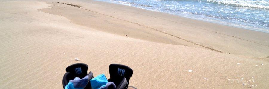 Wanderschuhe im Sand, rechts rollt das Mittelmeer heran