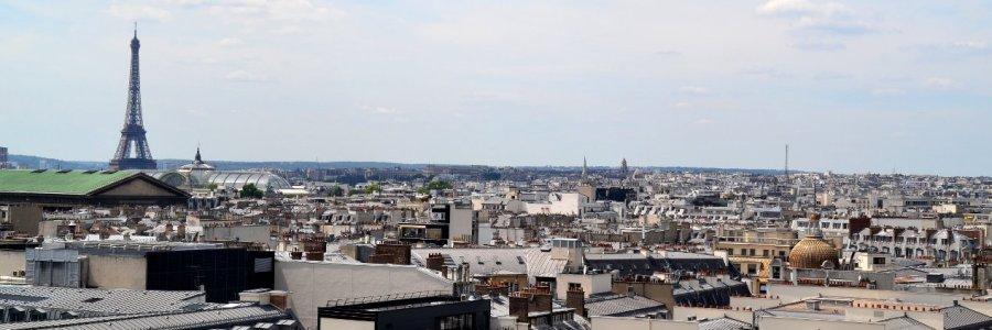 Blick über die Dächer von Paris, links sticht der Eiffelturm hoch in den blau-wolkigen Himmel
