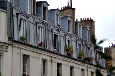 Eine Häuserfassade mit zwei Dachgeschossen in Paris