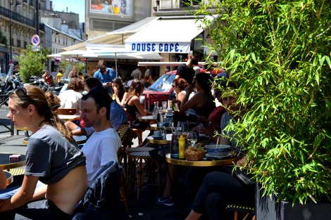 """Kleine Tische mit zur Straße ausgerichteten Stühlen stehen vor einem Bistro im 12. Stadtviertel. Die Plätze sind voll, auf den Tischen stehen Getränke und Speisen. Es ist ein sonniger Tag, und die Menschen sind sommerlich gekleidet. Im Hintergrund eine Markise, auf der """"Pause Café"""" geschrieben steht."""