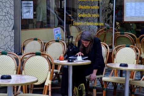 Eine ältere Frau, in schwarzer Kleidung und schwarzen Stiefeln mit neon-gelben Schnürsenkeln sitzt an einem Bistro-Tisch gebeugt über ihrem iPad