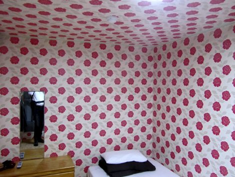 Hotelzimmer: Zwei Wände mit gleicher Tapete: weiß mit Muster von pinken Mohnblumen. Auch die Decke ist so tapeziert. Rechts das Ein-Mann-Bett, links eine Kommode, darüber ein einfacher Spiegel