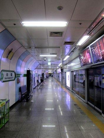 U-Bahn Station in Seoul: ein langer Gang, rechts Glastüren, die sich öffnen wenn ein Zug dort steht.