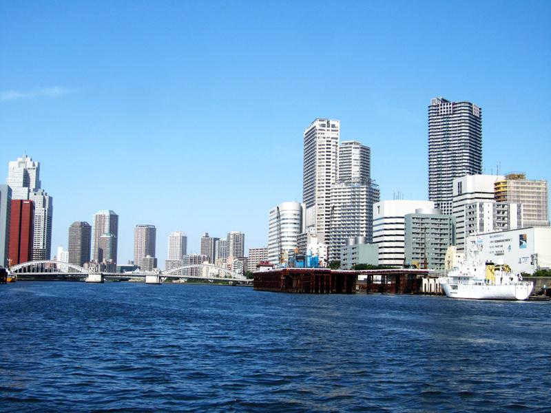 Blick über den Sumi-gawa Fluss vom Boot, blauer Himmel, links und rechts Hochhäuser, in der Ferne eine Stahlbrücke