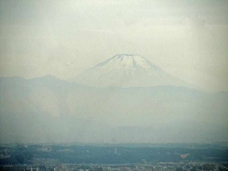 Dunstig, nur schwer zu erkennen, erhebt sich in weiter Ferne der Fuji; ein perfekt geformter Kegel