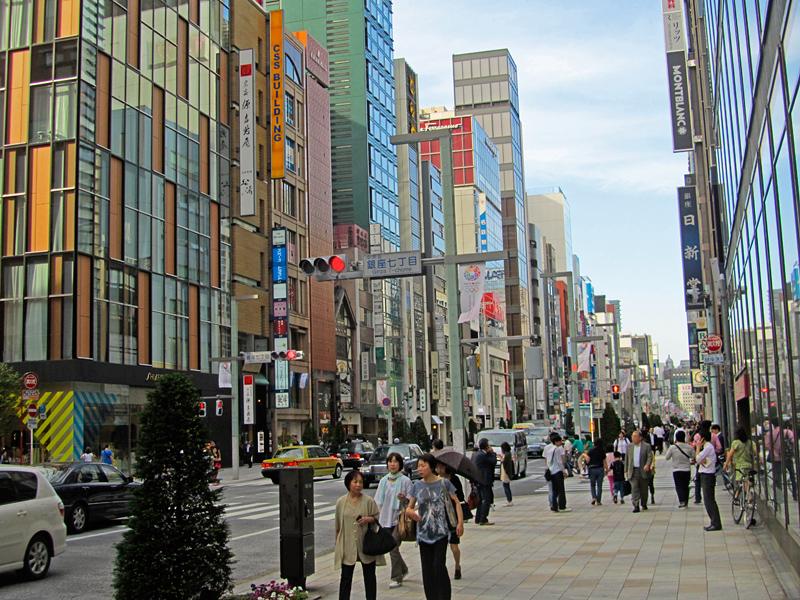 Die Ginza: links und rechts hohe, vielfarbene Kaufhäuser; links Autoverkehr, rechts Bürgersteig mit zahlreichen Passanten