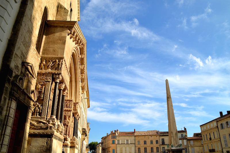 Ein Platz in Arles: links ein Kirchenportal, in der Mitte ein Obelisk; goldenes Abendlicht
