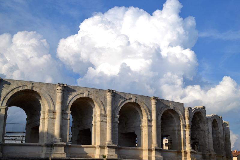 Die oberste Bogen-Reihe der römischen Arena von Arles - darüber dicke, weiße Wolkenberge