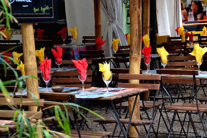 Kleine Tische für das Kulinarik-Festival - eingedeckt, in den Gläsern stecken rote und gelbe Servietten