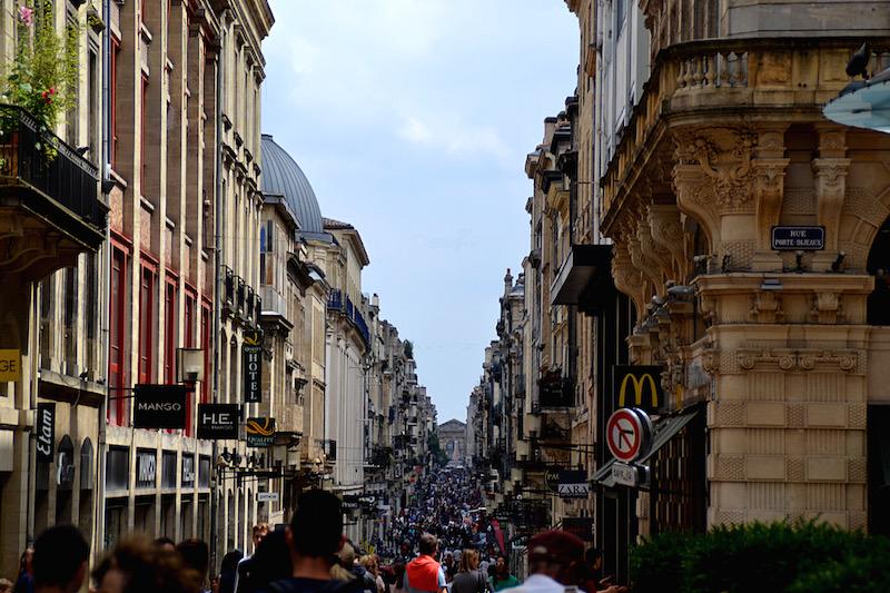 Die Hauptstraße von Bordeaux, voller Menschen (keine Autos) - mit Blick auf das Triumphtor am Ende