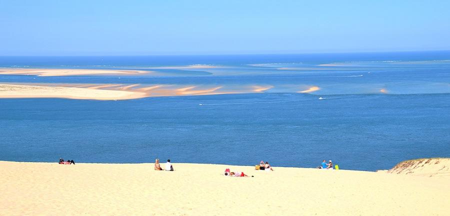 Der Blick von der Dune du Pilat auf den Atlantik: Menschen liegen im Sand, in der Ferne Sandbänke im Wasser