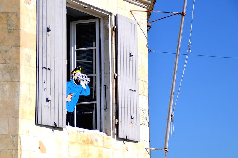 Kapitän Haddock aus Tim & Struppi blickt mit einem Fernglas aus dem zweiten Stock oberhalb des Comicladens in St. Martin, Ile de Ré