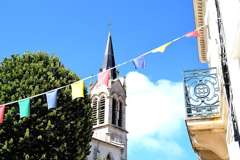 Bunte Fähnchen überspannen die Straße von Courade, auf der Ile de Ré - im Hintergrund: der Kirchturm des Dorfes