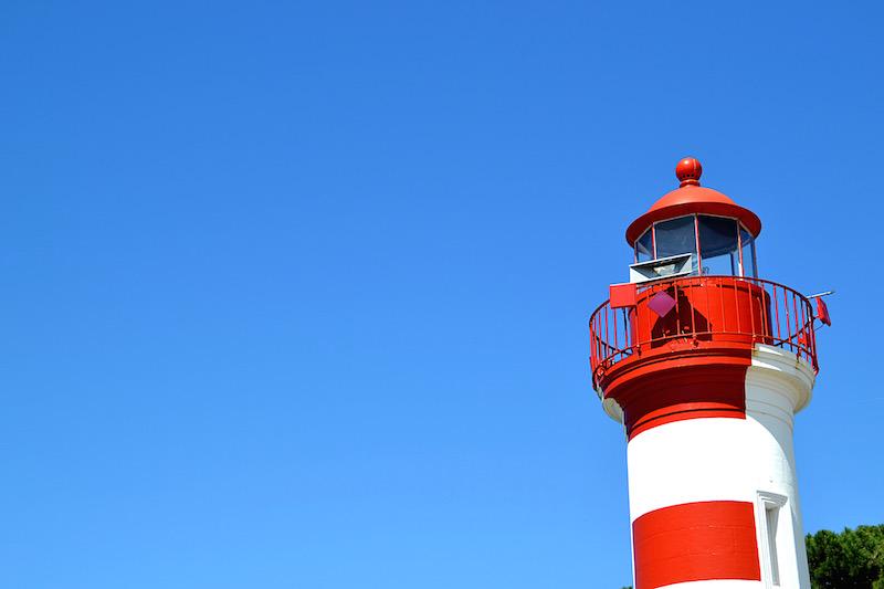 Blauer Himmel und rechts ein kleiner, rot-weiß-gestreifter Leuchtturm am Hafen von La Rochelle
