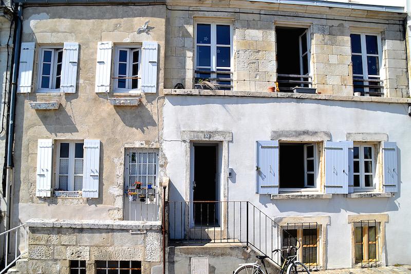 Weiße Häuserfassade mit blauen Fensterläden in La Rochelle