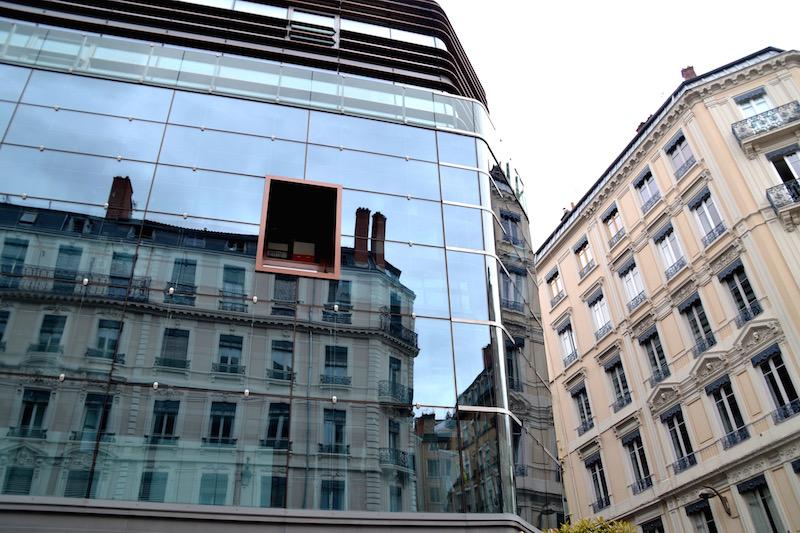 Die klassischen Gebäude des 19. Jahrhunderts spiegeln sich in der gläsernen Fassade eines modernen Hauses