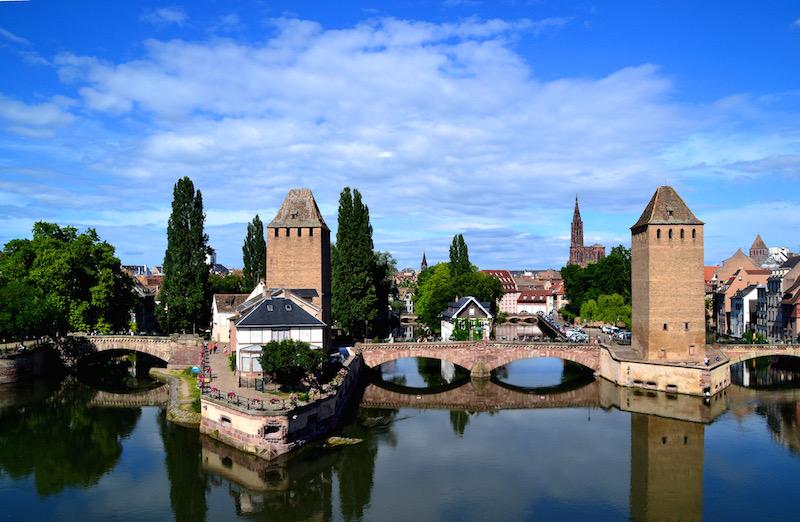 Die Silhouette von Straßburg vom Wasser aus: Zwei Wachtürme, durch eine steinerne Bogenbrücke verbunden; dahinter die Altstadt und in der Ferne erhebt sich das Münster