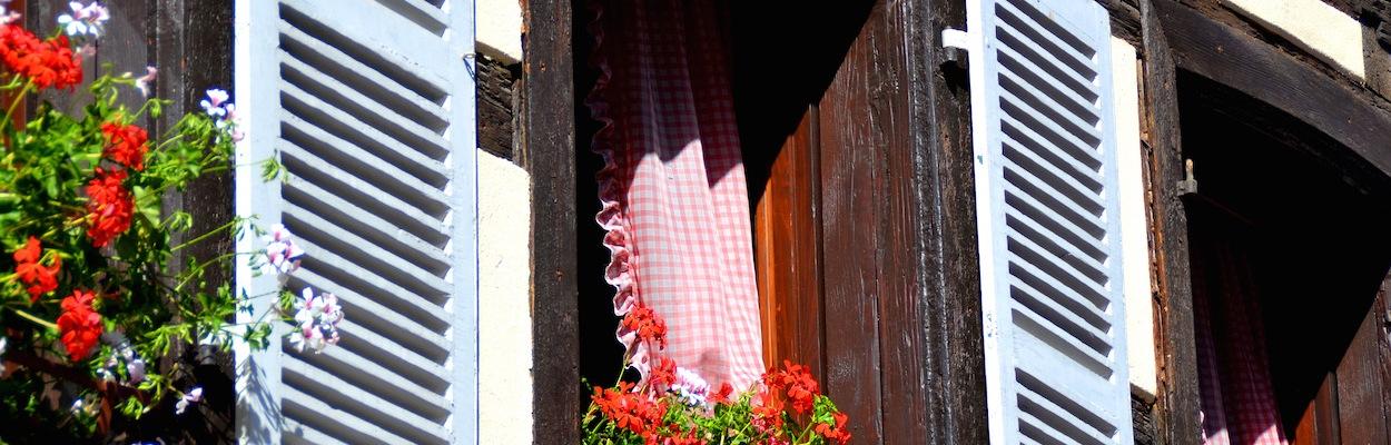 Die Fenster eines Fachwerkhauses: mit hellblauen Fensterladen, rot-weiß-karierten Gardinen und roten Geranien