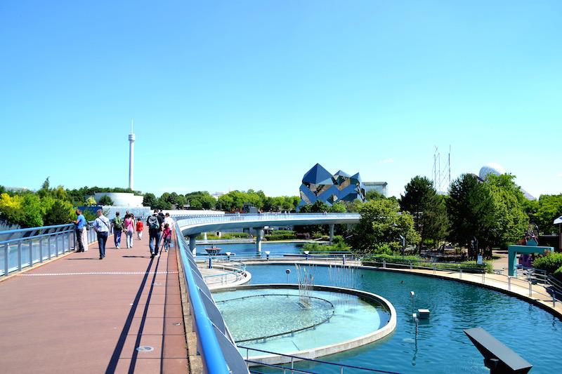 Blick über die zentrale, geschwungene Brücke von Futuroscope. Unter der Brücke die blaue Lagune des Parks, rechts im Hintergrund der gläserne Kristall