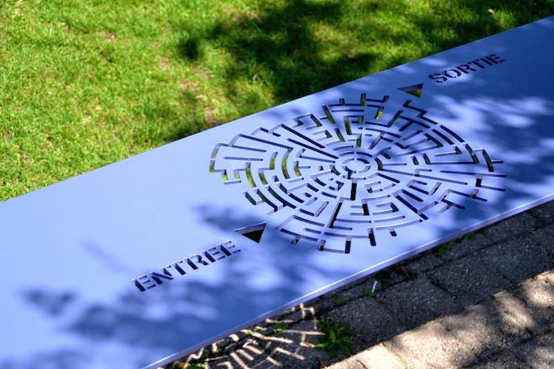 """Violette Parkbank im Futuroscope mit einem eingestanzten, runden Labyrinth; links steht """"Entree"""", rechts """"Sortie"""""""